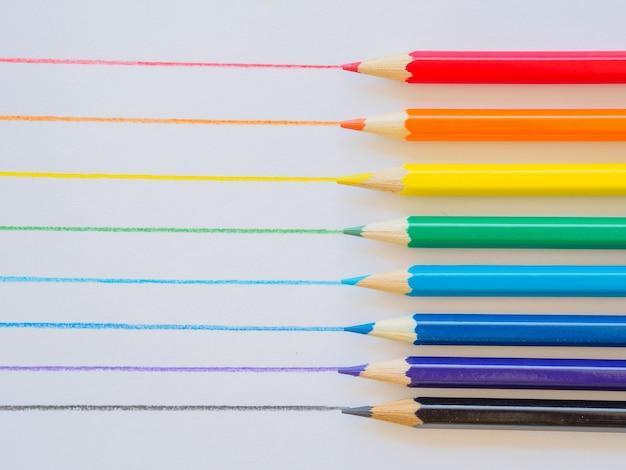 Matite colorate su carta bianca. materiale didattico a scuola, per sfondo e carta da parati.
