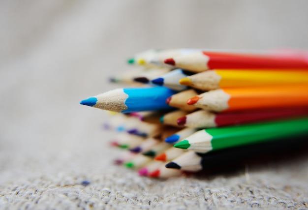 Matite colorate su sfondo di tela