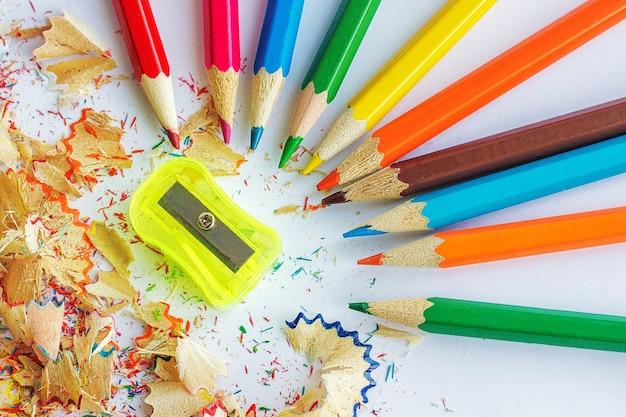 Matite colorate, trucioli di matite e un temperino