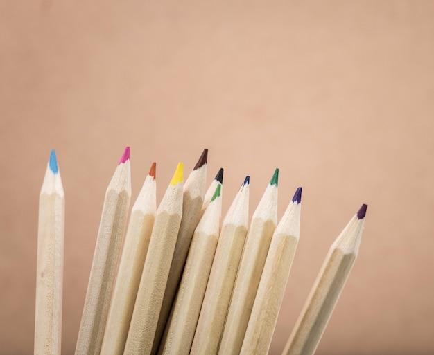 Matite di colori su fondo marrone. un gruppo di matite di legno colorate.
