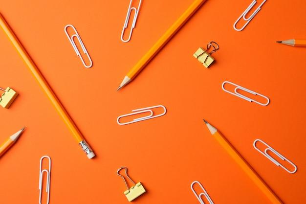 Matite e clip sulla tavola arancio, vista superiore