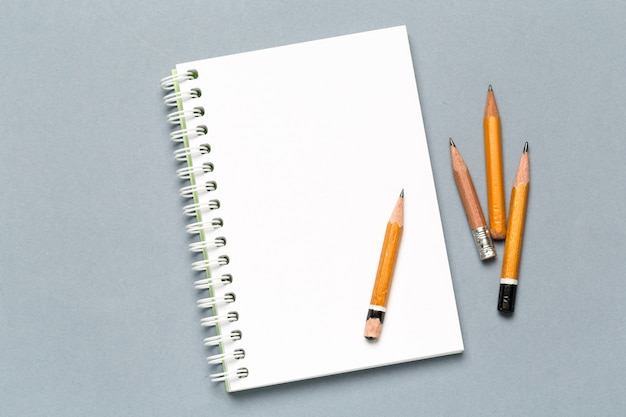 Matite e fogli di carta del blocco note sulla tavola grigia dello scrittorio