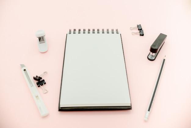 Matite, graffette, cucitrice meccanica e blocco note su sfondo rosa con spazio di copia.