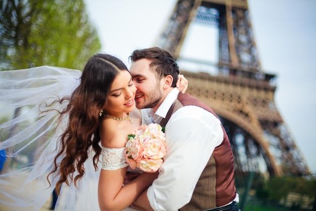 Matrimonio a parigi. felice coppia appena sposata che abbraccia vicino alla torre eiffel