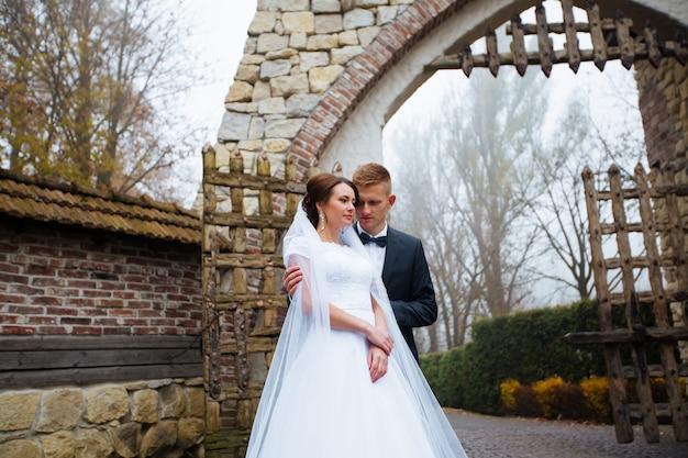 Matrimonio baciare sposi coppia di innamorati con bouquet di rose fiori al giorno nuziale invernale godetevi il momento di felicità e divertimento. giocoso sposi famiglia donna e uomo innamorato. bellissima sposa