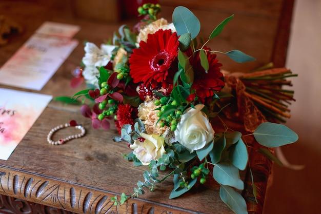 Matrimonio bouquet di fiori tra cui iperico rosso, rose, mughetti, mini rose, eucalipto con semi, astilbe, scabiosa, pieris ed edera