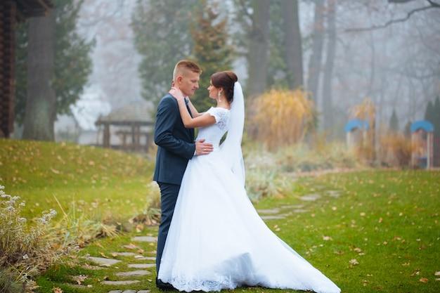Matrimonio, coppia bacio nelle colline vicino al fiume al tramonto. vento che svolazza un lungo velo. paesaggio di colline e montagne