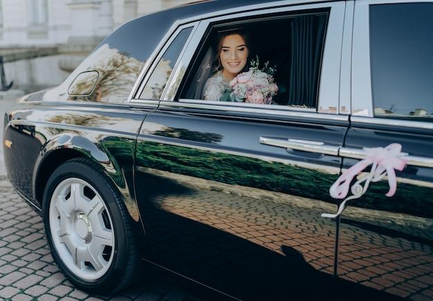 Matrimonio di lusso. sposa elegante splendida che posa in automobile nera di lusso alla moda, sedentesi dentro nel mazzo della tenuta del salone.