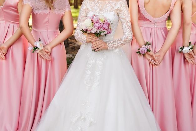 Matrimonio elegante e alla moda. sposa con bouquet da sposa e damigelle con piccoli mazzi sulle braccia. abito da sposa bianco e abiti da damigella d'onore rosa. matrimonio concettuale
