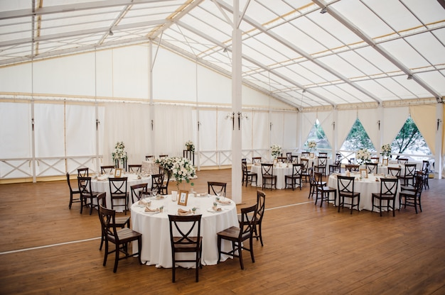 Matrimonio in tenda. decorazione della sala. tovaglie bianche, bellissimi decori e piatti.