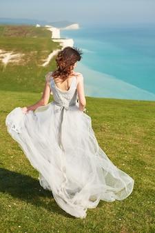 Matrimonio matrimonio al mare. una giovane sposa si allontana lungo una scogliera in riva al mare.