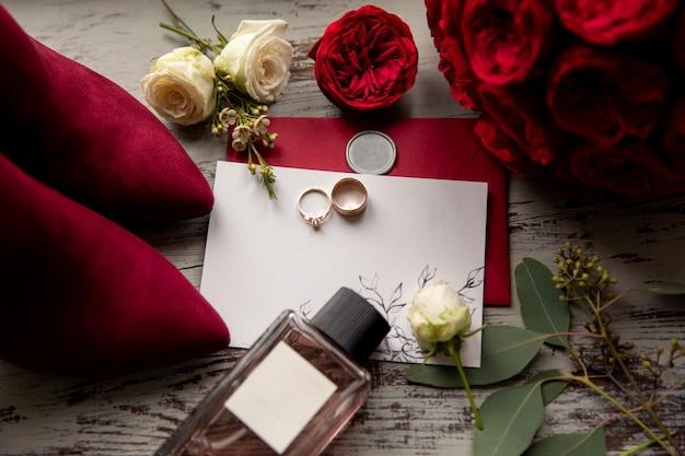 Matrimonio rosso. fedi nuziali su invito bianco e rosso vicino alla bottiglia di profumo