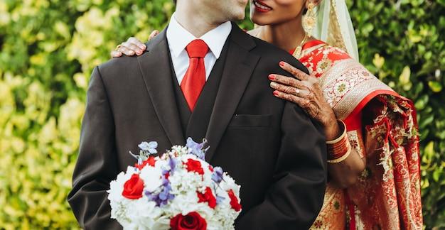 Matrimonio tradizionale indù la sposa abbraccia lo sposo tenero da dietro