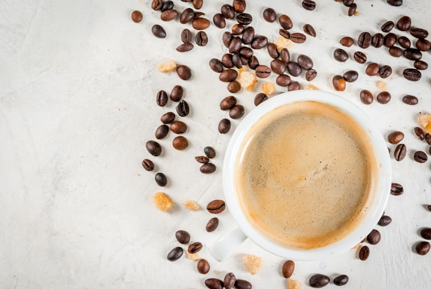 Mattina. cibo. chicchi di caffè, una tazza di caffè appena fatto e un cucchiaio di zucchero di canna marrone su un tavolo di pietra bianca. vista dall'alto