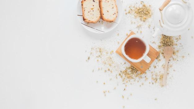 Mattina colazione pane e tè al limone con teiera in ceramica bianca