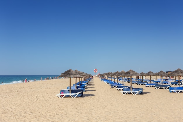 Mattina d'estate sulla spiaggia dell'isola di tavira. letti vuoti nella sabbia.