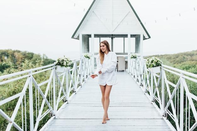 Mattina della sposa, bella donna bionda in camicia da uomo sulla terrazza estiva.