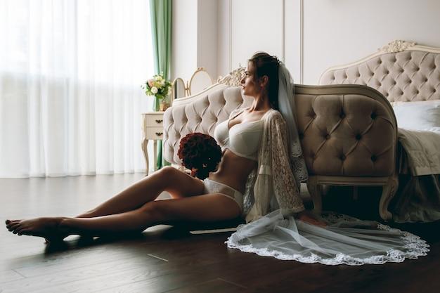 Mattina della sposa bella ragazza bionda sexy che posa in biancheria intima di pizzo bianco