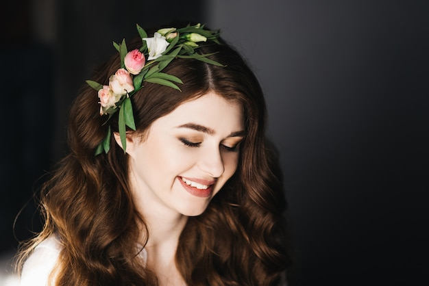 Mattina della sposa bellissimo ritratto di una sposa in una vestaglia con capelli ricci e fiori freschi