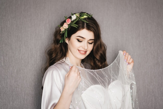 Mattina della sposa bellissimo ritratto di una sposa in una vestaglia con riccioli di capelli e fiori freschi vicino l'abito da sposa.