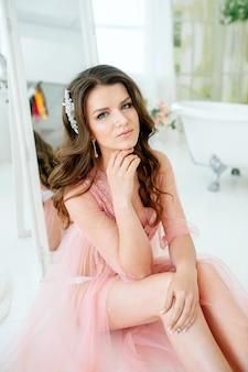 Mattina della sposa donna in un abito boudoir rosa trasparente e biancheria intima con una bella acconciatura in una stanza con un bagno vintage