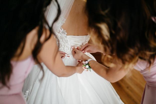 Mattina della sposa quando indossa un bellissimo vestito