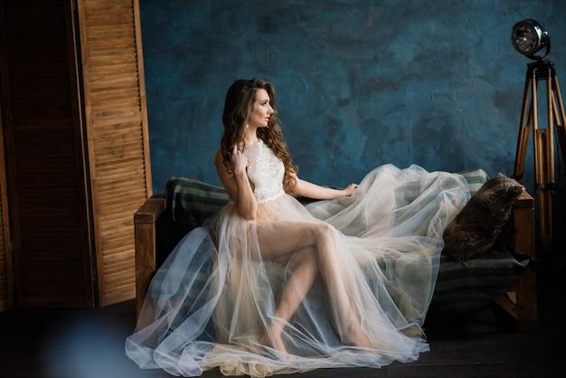 Mattina della sposa ragazza sexy che posa in biancheria intima di pizzo bianco. ritratto di una bellissima giovane femmina in un intimo bianco. donna seducente in lino bianco e vestaglia.