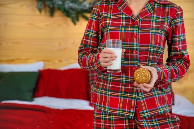 Mattina di natale, donna in pigiama con biscotti e un bicchiere di latte. messa a fuoco selettiva.