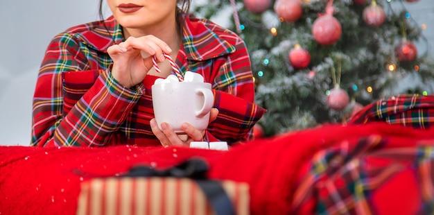 Mattina di natale, ragazza in pigiama con una tazza di cioccolata calda con marshmallow. messa a fuoco selettiva.