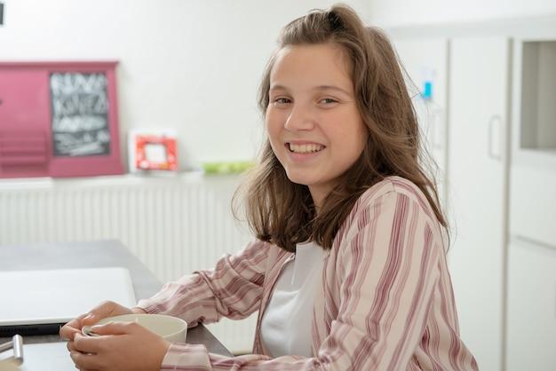 Mattina, ragazza adolescente sta bevendo il caffè in una ciotola
