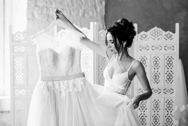 Mattina sposa con damigella d'onore. tiene in mano un bellissimo abito da sposa rosa. raccogliere. preparati per il matrimonio. foto in bianco e nero