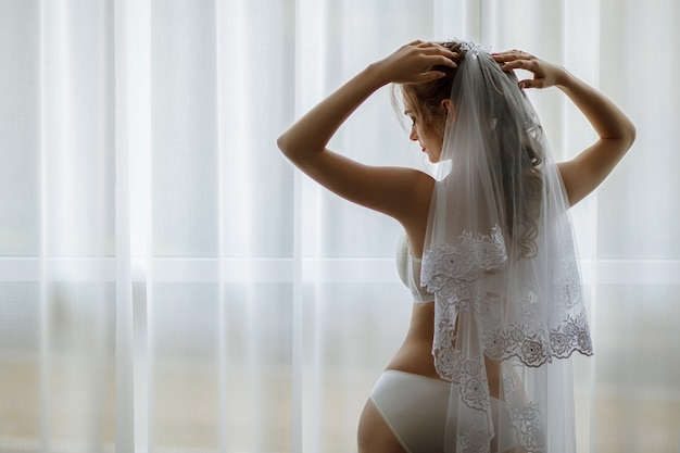 Mattina sposa. ritratto di matrimonio per la sposa. tiro al boudoir. la sposa in biancheria intima bianca bellissima.