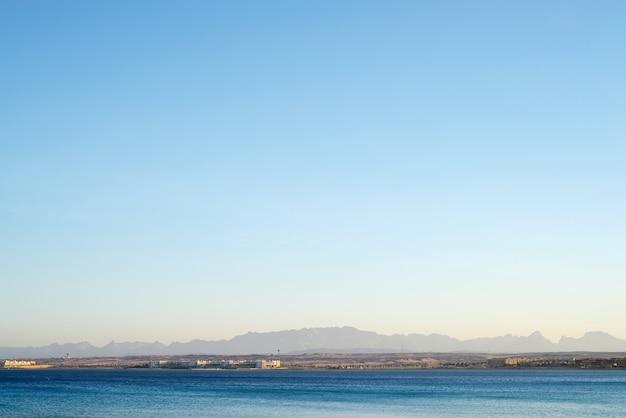 Mattina vista della costa con hotel dall'acqua.