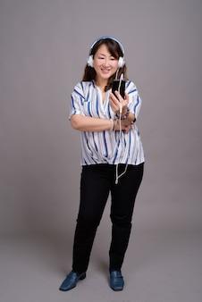 Matura bella donna d'affari asiatica con auricolari e telefono cellulare
