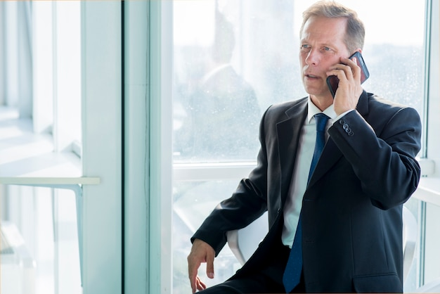 Maturo uomo d'affari parlando su smartphone