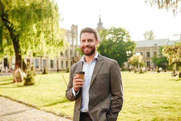Maturo uomo gioioso in abito classico grigio che beve caffè da asporto durante la passeggiata nel parco con erba e alberi