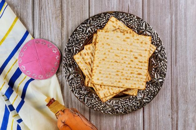 Matza, tallit e vino kosher in bottiglia su fondo di legno.