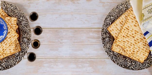 Matzos della celebrazione della pasqua ebraica con pane azzimo matzo sul bicchiere di vino kiddush