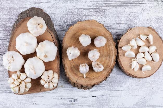 Mazzi di aglio su sottopentole su un tavolo di legno chiaro. vista dall'alto.
