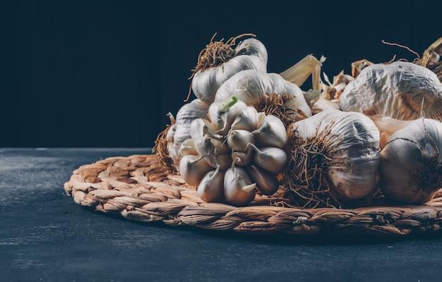 Mazzi di aglio su una vista laterale trivet