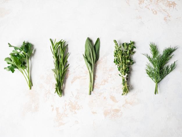 Mazzi di erbe fresche crude - rosmarino, timo, aneto, prezzemolo e salvia. vista dall'alto. copia spazio