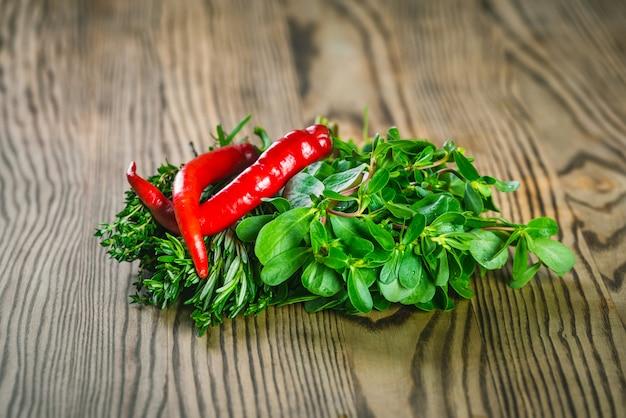 Mazzi di erbe fresche timo, insalata e rosmarino, peperoncino rosso su tavola di legno.