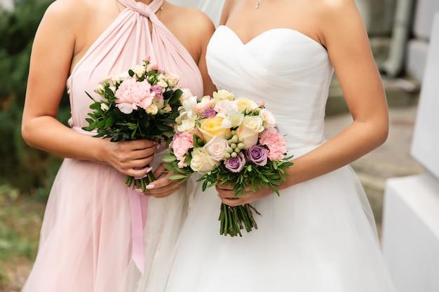 Mazzi di nozze della tenuta della damigella d'onore e della sposa