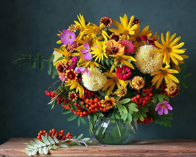Mazzo autunnale con fiori da giardino e rami di cenere di montagna.