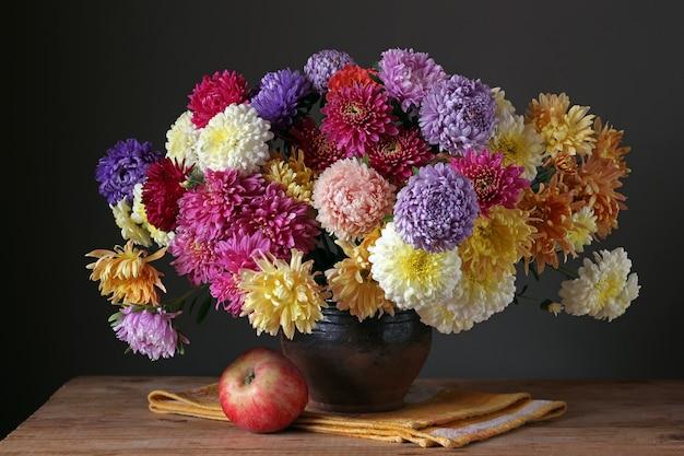 Mazzo autunnale di astri e crisantemi. natura morta con fiori e mela.