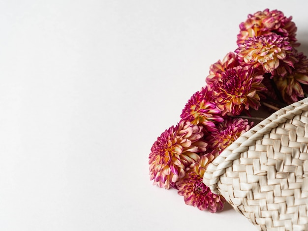 Mazzo autunnale di pesche stagionali e dalie rosa in un sacchetto di paglia di vimini