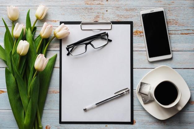 Mazzo bianco dei tulipani con la tazza di caffè, lo smartphone e il taccuino vuoto