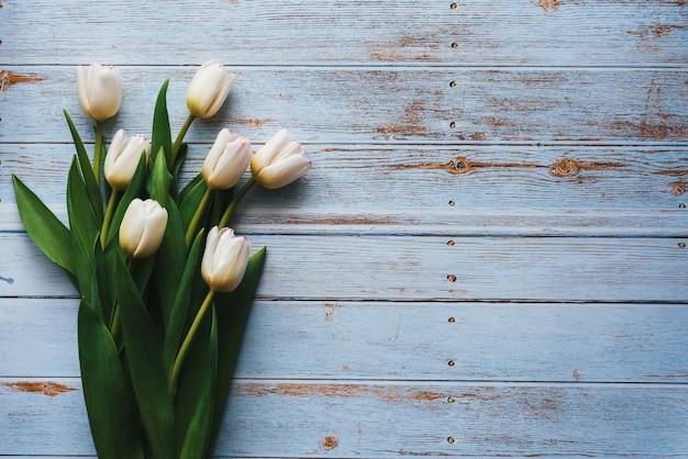 Mazzo bianco dei tulipani su fondo blu di legno. vista piana la composizione, vista dall'alto con spazio di copia
