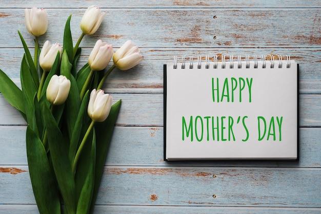 Mazzo dei fiori bianchi dei tulipani con un taccuino con la festa della mamma felice