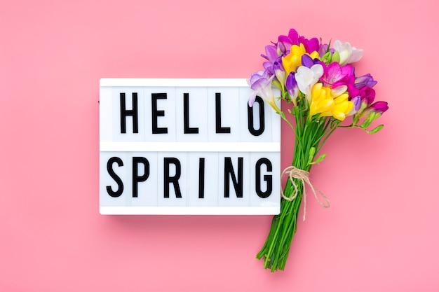 Mazzo dei fiori di fresia, lightbox con testo ciao primavera biglietto di auguri floreale vista dall'alto vista piana concetto di primavera